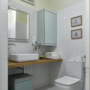 Новые идеи обустройства дома: ванная комната в стиле модернизм с плоскими фасадами, бирюзовыми фасадами, раздельным унитазом, белой плиткой, плиткой мозаикой, настольной раковиной, столешницей из дерева, белым полом и коричневой столешницей
