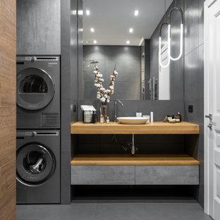 Exempel på ett mellanstort modernt en-suite badrum, med släta luckor, skåp i mellenmörkt trä, ett badkar i en alkov, en dusch/badkar-kombination, en vägghängd toalettstol, grå kakel, porslinskakel, grå väggar, klinkergolv i porslin, träbänkskiva, grått golv, dusch med duschdraperi och ett fristående handfat