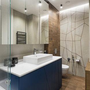Неиссякаемый источник вдохновения для домашнего уюта: ванная комната в современном стиле с синими фасадами, инсталляцией, настольной раковиной, коричневым полом и белой столешницей