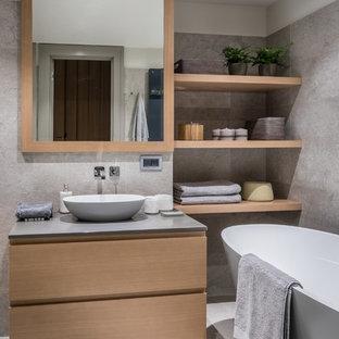 Выдающиеся фото от архитекторов и дизайнеров интерьера: главная ванная комната среднего размера в современном стиле с отдельно стоящей ванной, серой плиткой, мраморной плиткой, мраморным полом, настольной раковиной, серым полом, плоскими фасадами, фасадами цвета дерева среднего тона и серой столешницей