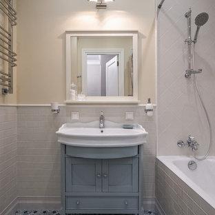 Стильный дизайн: ванная комната в классическом стиле с фасадами островного типа, синими фасадами, ванной в нише, душем над ванной, белой плиткой, бежевыми стенами, полом из керамической плитки, душевой кабиной, монолитной раковиной, разноцветным полом и шторкой для ванной - последний тренд