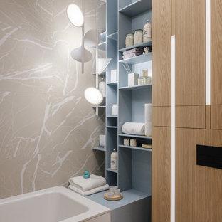 Foto de cuarto de baño infantil, actual, con bañera empotrada, baldosas y/o azulejos beige, armarios abiertos, puertas de armario grises y losas de piedra