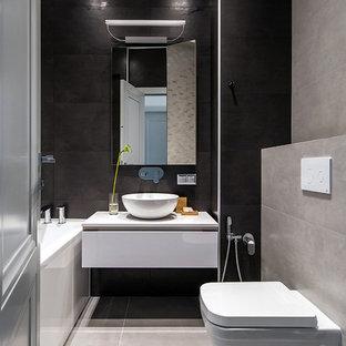 Стильный дизайн: маленькая главная ванная комната в современном стиле с плоскими фасадами, белыми фасадами, ванной в нише, инсталляцией, серой плиткой, черной плиткой, настольной раковиной и серым полом - последний тренд