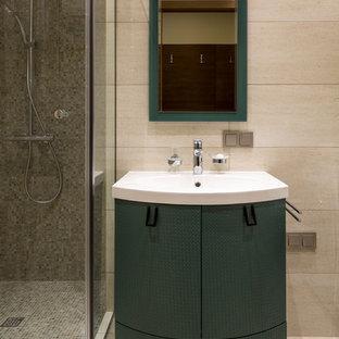 Пример оригинального дизайна: ванная комната в современном стиле с зелеными фасадами, бежевой плиткой, душевой кабиной, монолитной раковиной и бежевым полом
