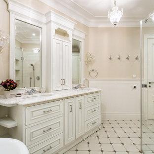 Новый формат декора квартиры: ванная комната в стиле современная классика с фасадами с выступающей филенкой, белыми фасадами, бежевыми стенами, врезной раковиной, белым полом и белой столешницей