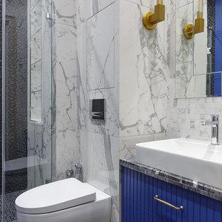 Foto de cuarto de baño con ducha, tradicional renovado, de tamaño medio, con puertas de armario azules, ducha empotrada, sanitario de pared, baldosas y/o azulejos negros, baldosas y/o azulejos grises, baldosas y/o azulejos de porcelana, suelo de baldosas de porcelana, lavabo sobreencimera, encimera de cuarcita, suelo negro, ducha con puerta corredera, encimeras negras y armarios con paneles lisos