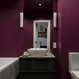 Создайте стильный интерьер: главная ванная комната в современном стиле с плоскими фасадами, раздельным унитазом, фиолетовыми стенами, настольной раковиной и черным полом - последний тренд