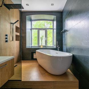 На фото: ванная комната в современном стиле с плоскими фасадами, фасадами цвета дерева среднего тона, отдельно стоящей ванной, черной плиткой, паркетным полом среднего тона, настольной раковиной, коричневым полом, белой столешницей, тумбой под одну раковину и подвесной тумбой с