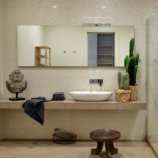 На фото: ванная комната в стиле фьюжн с бежевой плиткой и настольной раковиной с