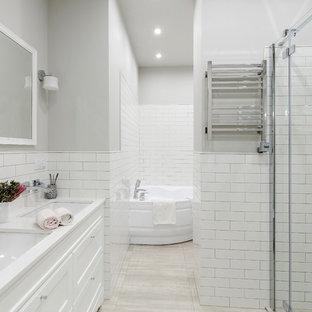 Стильный дизайн: большая главная ванная комната в стиле современная классика с угловой ванной, угловым душем, белой плиткой, плиткой кабанчик, серыми стенами, врезной раковиной, столешницей из искусственного кварца, душем с распашными дверями, белой столешницей, фасадами с утопленной филенкой, белыми фасадами и серым полом - последний тренд
