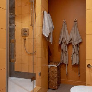 На фото: ванная комната в современном стиле с душем в нише, оранжевой плиткой, оранжевыми стенами, душевой кабиной и душем с распашными дверями с