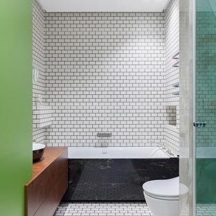 На фото: главные ванные комнаты в современном стиле с плоскими фасадами, фасадами цвета дерева среднего тона, ванной в нише, душем в нише, инсталляцией, белой плиткой, настольной раковиной и белым полом
