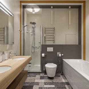 Идея дизайна: главная ванная комната среднего размера в современном стиле с серой плиткой, плиткой из листового камня, плоскими фасадами, светлыми деревянными фасадами, ванной в нише, угловым душем, инсталляцией, белыми стенами, врезной раковиной, столешницей из дерева, серым полом, душем с распашными дверями и бежевой столешницей