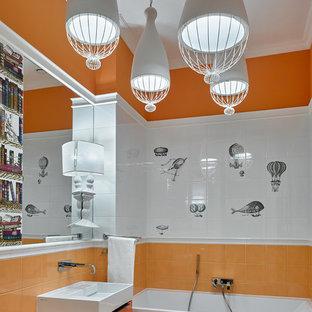 Modelo de cuarto de baño infantil, contemporáneo, con armarios con paneles lisos, puertas de armario naranjas, bañera empotrada, parades naranjas, suelo de baldosas de cerámica, baldosas y/o azulejos blancos, baldosas y/o azulejos naranja y lavabo integrado