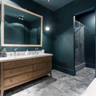 На фото: большая главная ванная комната в стиле неоклассика (современная классика) с фасадами островного типа, фасадами цвета дерева среднего тона, отдельно стоящей ванной, душем в нише, зелеными стенами, врезной раковиной, серым полом, душем с распашными дверями, белой столешницей, тумбой под две раковины и встроенной тумбой