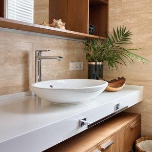 Свежая идея для дизайна: ванная комната в современном стиле с плоскими фасадами, светлыми деревянными фасадами, бежевой плиткой, бежевыми стенами, настольной раковиной и белой столешницей - отличное фото интерьера