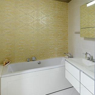 На фото: главная ванная комната в современном стиле с плоскими фасадами, белыми фасадами, ванной в нише, белой плиткой, желтой плиткой, раковиной с несколькими смесителями и белым полом с