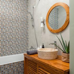 Пример оригинального дизайна: ванная комната среднего размера в стиле фьюжн с фасадами с филенкой типа жалюзи, фасадами цвета дерева среднего тона, ванной в нише, разноцветной плиткой, керамической плиткой, столешницей из дерева, коричневой столешницей, душем над ванной, настольной раковиной и шторкой для душа