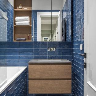 На фото: главная ванная комната в современном стиле с плоскими фасадами, фасадами цвета дерева среднего тона, ванной в нише, душем над ванной, синей плиткой, врезной раковиной, разноцветным полом и серой столешницей