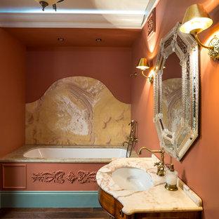 Ispirazione per una stanza da bagno padronale boho chic con ante in legno bruno, vasca sottopiano, piastrelle gialle, lastra di pietra, pareti arancioni, lavabo sottopiano e top in marmo