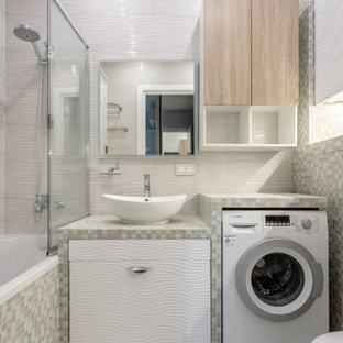 Неиссякаемый источник вдохновения для домашнего уюта: маленькая ванная комната в современном стиле с плоскими фасадами, белыми фасадами, ванной в нише, душем над ванной, инсталляцией, бежевой плиткой, душевой кабиной, настольной раковиной и разноцветной столешницей
