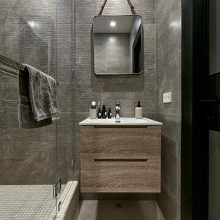 Стильный дизайн: ванная комната в современном стиле с плоскими фасадами, фасадами цвета дерева среднего тона, серой плиткой, душевой кабиной, монолитной раковиной, тумбой под одну раковину и подвесной тумбой - последний тренд
