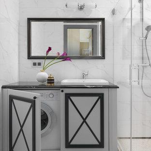 На фото: ванные комнаты в современном стиле с белой плиткой, душевой кабиной, накладной раковиной, белым полом, черной столешницей, серыми фасадами, угловым душем, белыми стенами и душем с распашными дверями