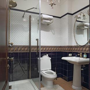 Пример оригинального дизайна интерьера: ванная комната среднего размера в классическом стиле с раздельным унитазом, синей плиткой, керамической плиткой, белыми стенами, полом из керамогранита, раковиной с пьедесталом, угловым душем, душевой кабиной и душем с распашными дверями