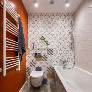 На фото: ванная комната в современном стиле с инсталляцией, оранжевыми стенами и серым полом с