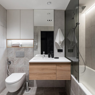 Пример оригинального дизайна: главная ванная комната в современном стиле с плоскими фасадами, ванной в нише, душем над ванной, инсталляцией, серой плиткой, врезной раковиной, серым полом, белой столешницей, светлыми деревянными фасадами, серыми стенами, тумбой под одну раковину и подвесной тумбой