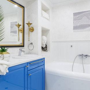 Свежая идея для дизайна: ванная комната в современном стиле с фасадами с выступающей филенкой, синими фасадами, ванной в нише, белыми стенами, накладной раковиной, белой столешницей, тумбой под одну раковину и панелями на стенах - отличное фото интерьера