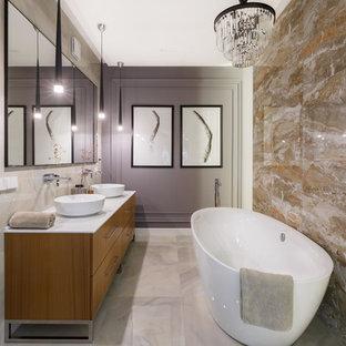 Пример оригинального дизайна: главная ванная комната в современном стиле с плоскими фасадами, фасадами цвета дерева среднего тона, отдельно стоящей ванной, бежевой плиткой, серыми стенами, настольной раковиной, серым полом и белой столешницей