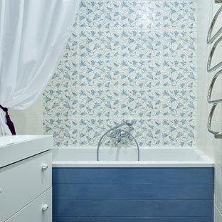 Пример оригинального дизайна интерьера: главная ванная комната в классическом стиле с плоскими фасадами, белыми фасадами, ванной в нише, душем над ванной, разноцветной плиткой, синими стенами, монолитной раковиной и шторкой для душа
