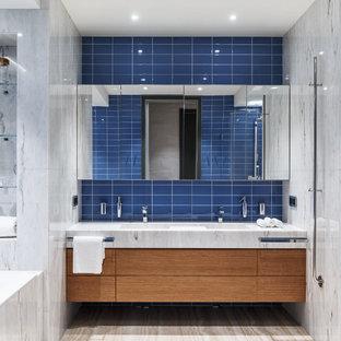 Exempel på ett stort modernt vit vitt badrum för barn, med släta luckor, skåp i mellenmörkt trä, ett undermonterat badkar, en hörndusch, en vägghängd toalettstol, blå kakel, keramikplattor, blå väggar, travertin golv, ett avlångt handfat, marmorbänkskiva, beiget golv och dusch med gångjärnsdörr