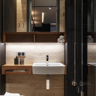 Modelo de cuarto de baño con ducha, actual, pequeño, con armarios con paneles lisos, puertas de armario de madera oscura, ducha empotrada, baldosas y/o azulejos de pizarra, suelo de travertino, encimera de madera, suelo beige, ducha con puerta con bisagras y lavabo encastrado