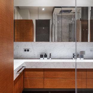 Großes Modernes Badezimmer En Suite mit flächenbündigen Schrankfronten, hellbraunen Holzschränken, Eckdusche, Bidet, weißen Fliesen, Marmorfliesen, weißer Wandfarbe, braunem Holzboden, Unterbauwaschbecken, Marmor-Waschbecken/Waschtisch, braunem Boden, Falttür-Duschabtrennung und weißer Waschtischplatte in Moskau