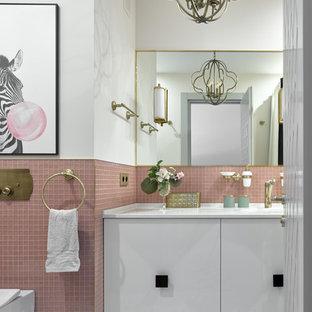Diseño de cuarto de baño clásico renovado con armarios con paneles lisos, puertas de armario blancas, sanitario de pared, baldosas y/o azulejos rosa, baldosas y/o azulejos en mosaico, paredes blancas, suelo gris y encimeras blancas