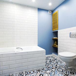 Новый формат декора квартиры: маленькая ванная комната в скандинавском стиле с плоскими фасадами, белыми фасадами, душем над ванной, инсталляцией, керамической плиткой, полом из керамической плитки, столешницей из дерева, разноцветным полом, белой плиткой, синими стенами, настольной раковиной и коричневой столешницей