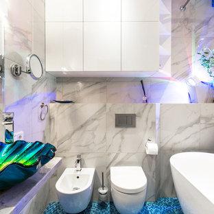Foto di una piccola stanza da bagno per bambini design con ante lisce, ante bianche, vasca freestanding, WC sospeso, piastrelle a mosaico, pareti bianche, pavimento con piastrelle a mosaico, top in superficie solida, pavimento blu, top bianco, piastrelle grigie e lavabo a bacinella