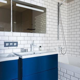 На фото: главные ванные комнаты в современном стиле с плоскими фасадами, синими фасадами, белой плиткой, плиткой кабанчик, серыми стенами и накладной раковиной