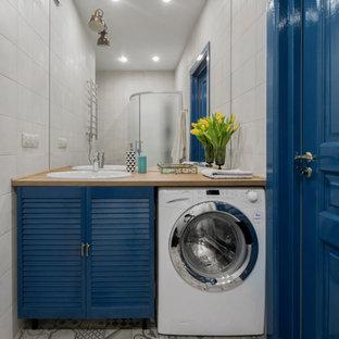 Modelo de cuarto de baño contemporáneo con armarios con puertas mallorquinas, puertas de armario azules, ducha esquinera, baldosas y/o azulejos grises, paredes grises, suelo de baldosas de cerámica y encimera de laminado