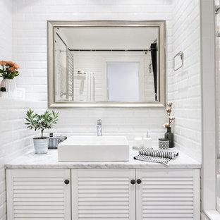 Идея дизайна: главная ванная комната в современном стиле с фасадами с филенкой типа жалюзи, белыми фасадами, ванной в нише, душем над ванной, белой плиткой, плиткой кабанчик, настольной раковиной, мраморной столешницей и шторкой для душа