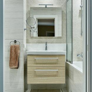 На фото: маленькая ванная комната в современном стиле с плоскими фасадами, светлыми деревянными фасадами, ванной в нише, душем над ванной, бежевой плиткой, бежевыми стенами, бежевым полом и бежевой столешницей с