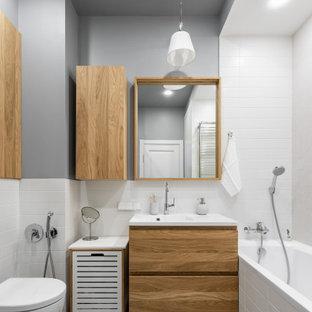 Идея дизайна: ванная комната среднего размера в скандинавском стиле с плоскими фасадами, коричневыми фасадами, ванной в нише, угловым душем, инсталляцией, белой плиткой, керамической плиткой, серыми стенами, полом из керамической плитки, раковиной с пьедесталом, столешницей из искусственного камня, серым полом, душем с раздвижными дверями и белой столешницей