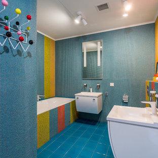 Modelo de cuarto de baño infantil, actual, de tamaño medio, con bañera empotrada, urinario, baldosas y/o azulejos en mosaico, suelo de baldosas de cerámica, armarios con paneles lisos, puertas de armario blancas, baldosas y/o azulejos azules, baldosas y/o azulejos multicolor y lavabo integrado