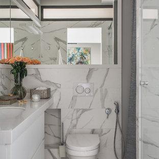 На фото: маленькая ванная комната в скандинавском стиле с плоскими фасадами, белыми фасадами, инсталляцией, белой плиткой, серой плиткой, разноцветной плиткой, серыми стенами, душевой кабиной, врезной раковиной, белой столешницей и разноцветным полом
