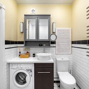 Идея дизайна: маленькая ванная комната в классическом стиле с плоскими фасадами, темными деревянными фасадами, белой плиткой, плиткой кабанчик, желтыми стенами, настольной раковиной, разноцветным полом, белой столешницей, тумбой под одну раковину, встроенной тумбой и стиральной машиной