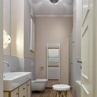 На фото: главная ванная комната в стиле фьюжн с ванной в нише, серой плиткой, бежевыми стенами, напольной тумбой, плоскими фасадами, белыми фасадами, душем в нише, полом из плитки под дерево, консольной раковиной, коричневым полом и тумбой под одну раковину с