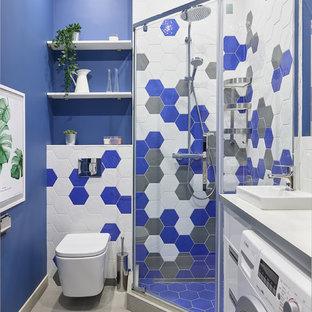 Diseño de cuarto de baño con ducha, actual, con armarios con paneles lisos, puertas de armario blancas, ducha esquinera, sanitario de pared, baldosas y/o azulejos azules, baldosas y/o azulejos blancos, baldosas y/o azulejos grises, paredes azules, lavabo encastrado, suelo gris, ducha con puerta con bisagras y encimeras blancas