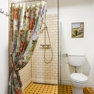 Réalisation d'une petit salle d'eau champêtre avec un placard avec porte à panneau surélevé, des portes de placard blanches, une douche à l'italienne, un WC séparé, un carrelage beige, des carreaux de céramique, un mur beige, un sol en carrelage de porcelaine, un plan vasque, un sol jaune et aucune cabine.